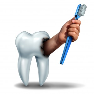 Brushing teeth concept as a human tooth with a cavity as a hand emerging out holding a generic toothbrush or tooth brush as a dental health care symbol for oral hygiene to avoid cavities on teeth.